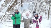 wintertime : Winter forest. Cheerful children in bright clothes blow up christmas crackers
