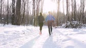 Winter forest. Young man and woman running in the morning woods. Beautiful sunlight