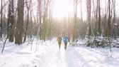 Winter forest. Young man and woman running in the morning woods. Beautiful morning sunlight
