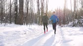 Winter forest. Young man and woman running on the trail in the morning park. Beautiful sunlight