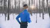 Young man and woman running in winter forest at early morning. Side view