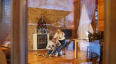 manžel : Young happy family with little baby sitting on the floor in cozy house. View from the window Dostupné videozáznamy