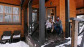 Young family drinking hot drinks on the veranda of a beautiful house Стоковые видеозаписи
