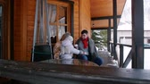 Young family with a little baby drinking hot drinks on the veranda of a beautiful house Стоковые видеозаписи