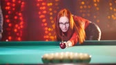 baize : Concentrated ginger woman playing billiard in billiard club. Breaks down arranged balls