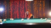 baize : Billiards club. Concentrated ginger woman in glasses aiming and hitting the ball Stock Footage