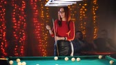 végszó : An attractive woman standing in billiard club rubbing chalk on a cue, while two men drinking beer on the background