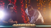 excitação : Two men standing by the billiards table, discuss the game tactics and one of the men hit the ball