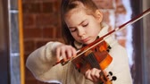 artisti : A little girl in white sweater learning how to play violin