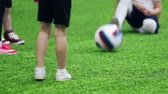bolas : Indoor football arena. Little child kicking the ball and girl catches it with her hands Stock Footage
