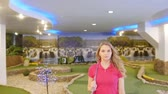 cursos : A young woman playing mini golf. Walking on the field looking in the camera