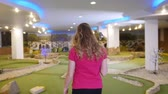 golfing : Playing mini golf. A young blonde woman takes a golf stick from the bag and goes away