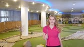 golfing : A young woman playing mini golf. Walking on the field