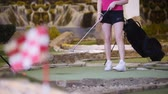 golfing : A young woman playing mini golf. Finishing flag on the blured foreground Stock Footage