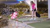 golfing : A young woman playing mini golf. A woman hitting several golf balls in a row Stock Footage