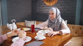 kafeterya : A muslim woman sitting in a cafe at the table, drinking juice and talking