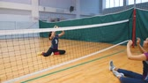 corajoso : Sports for disabled people. Two young women sitting on the gym floor and playing volleyball Stock Footage