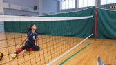 scopo : Sports for disabled people. A young woman sitting on the gym floor and playing volleyball with her trainer