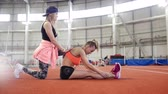 sportovkyně : Two young athletic women doing sport exercises. Doing stretching Dostupné videozáznamy