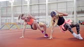 estiramiento : Two young athletic women doing sport exercises on their legs Archivo de Video