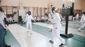 фехтование : 27 MARCH 2019. KAZAN, RUSSIA: Teenage girls in white protective clothes fighting on a fencing tournament in the hall Стоковые видеозаписи