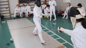 lunge : 27 MARCH 2019. KAZAN, RUSSIA: Teenage girls fencers in white protective clothes training their fighting