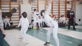 lunge : 27 MARCH 2019. KAZAN, RUSSIA: Teenage girls in white protective clothes fighting on a fencing tournament in the school hall