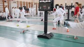 фехтование : 27 MARCH 2019. KAZAN, RUSSIA: Teenage girls in protective clothes fighting on a fencing tournament in the school hall