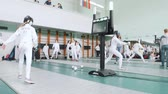 фехтование : 27 MARCH 2019. KAZAN, RUSSIA: Teenagers in protective clothes fighting on a fencing tournament in the school hall. A girl gets a point Стоковые видеозаписи