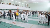 фехтование : 27 MARCH 2019. KAZAN, RUSSIA: A big tournament in the hall with many people. Teenagers fencers in protective clothes fighting Стоковые видеозаписи