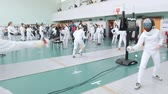 lunge : 27 MARCH 2019. KAZAN, RUSSIA: A big tournament in the hall with many people. Teenagers fencers in white protective clothes fighting