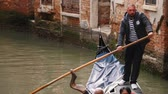 폭이 좁은 : 29-04-2019 ITALY, VENICE: A man guide people on the boat on a water channel in Venice