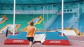 versenyképes : KAZAN, RUSSIA 26-07-2019: a man in orange shirt running up and leans on a pole to jump over the bar - pole vault training on stadium