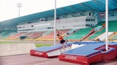 преуспевать : KAZAN, RUSSIA 26-07-2019: pole vault training - A young athletic woman jumps over the bar and her colleagues watching her - bad attempt