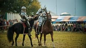 combativo : BULGAR, RUSSIA 11-08-2019: Knights in metal armor having a battle on wooden swords on the field - people watching behind the fence - medieval festival