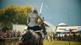 adversidade : BULGAR, RUSSIA 11-08-2019: Knight riding a horse on the field - holding a spear and raises it up