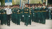 saksofon : RUSSIA, KAZAN 09-08-2019: A wind instrument parade - military musicians in green costumes marching on the street holding musical instruments - a man holding a nameplate says Rostov-on-Don Orchestra