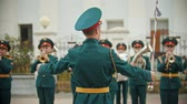 trompet : RUSSIA, KAZAN 09-08-2019: A wind instrument parade - people in green costumes listening to the kapellmeister