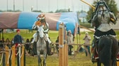 combativo : BULGAR, RUSSIA 11-08-2019: Knights having a battle on the field - running on each other and breaking the plastic spear because of the armor -medieval festival