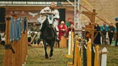 cavaleiro : BULGAR, RUSSIA 11-08-2019: Knight riding through the path and takes the ring from the fence