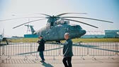 戦闘機 : 30 AUGUST 2019 MOSCOW, RUSSIA: an outdoors airplane exposition - businessmen in suits walking by the helicopter