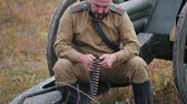 trou de balle : RUSSIA, REPUBLIC OF TATARSTAN 30-09-2019: A reconstruction of military operations in Russia in 1917 - A man soldier prepares the ammunition for charging in the machine gun