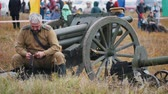 trou de balle : RUSSIA, KAZAN 30-09-2019: A reconstruction of military operations in Russia in 1917 - A man soldier prepares the ammunition for charging in the machine gun - people watching him