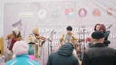 flet : RUSSIA, REPUBLIC OF TATARSTAN 30-09-2019: A reconstruction of military operations in Russia in 1917 - A music band playing on stage on the festival outdoors - a man playing flute and another singing in the microphone