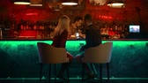 внимание : A bewitching couple having a date in the bar - bartender doing his job and the couple looking at the pictures in the phone