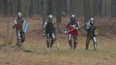 cavaleiro : Four men knightes walking in the row in the forest in full armour