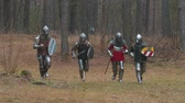 lovagi torna : Four men knightes running in the row in the forest in full armour holding weapons Stock mozgókép