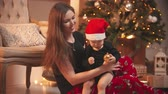 překvapení : Christmas concept - A smiling woman playing with her little baby son - the baby holding golden christmas ball