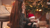 halı : Christmas concept - A young woman playing with her little baby in christmas studio - a baby holding toy deer