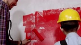 muren : Happy family repair the apartment - little boy and his father painting wall in red color Stockvideo